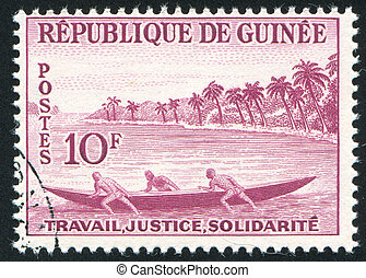 Launching fishing pirogue - GUINEA CIRCA 1959: stamp printed...