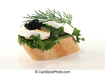 Canape with salad, quail eggs and caviar on white background