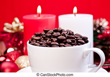 Christmas coffee beans in a cup over red background and...