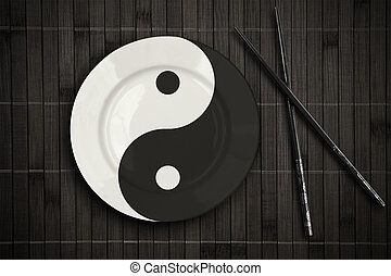 yin yan plate over bamboo placemat setting with sticks