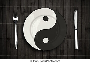 yin yan plate over bamboo placemat setting with fork and...