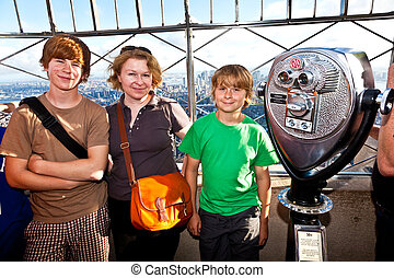 family on platform of Empire State building enjoys the...