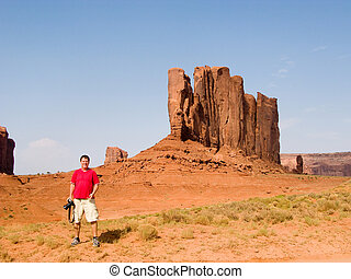 famous scenic Butte in Monument Valley - Tourist in front of...