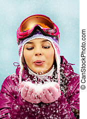 Fun - Portrait of a girl blowing snow out of hands against...