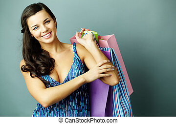 Good shopping - Portrait of happy brunette with paperbags...