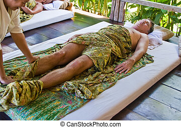 european man gets a healthy massage in thailand and enjoys...
