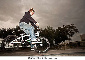 young red haired boy is jumping with his BMX Bike at the...