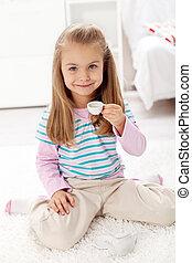 Litlle girl having tea