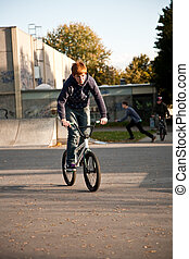 joung red haired boy is jumping with his BMX Bike at the...