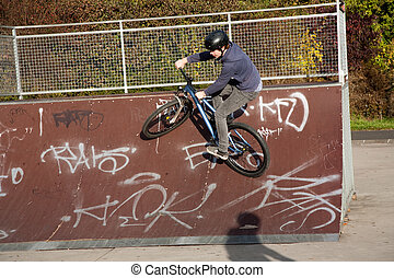 boy is biking with the dirtbike in a bike park at the...