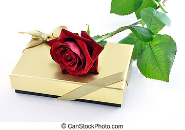 Red rose on a golden gift box