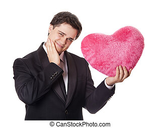 A man holding toy heart in formal black tux with tie isolated on white background