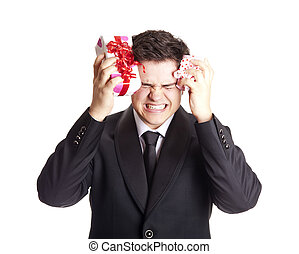 A angry man holding present box in formal black tux with tie...