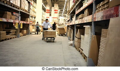 Warehouse. Man takes a box. - Warehouse. Man comes closer to...