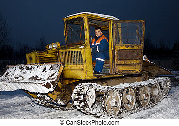 Tractor clearing snow at night. Tracked vehicles.