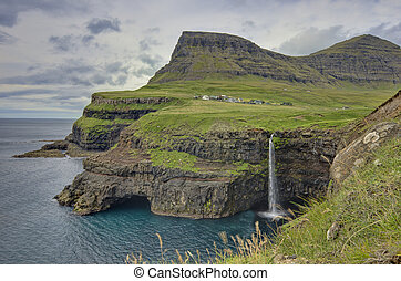 Steep green hills in the Faroe Islands - The village...
