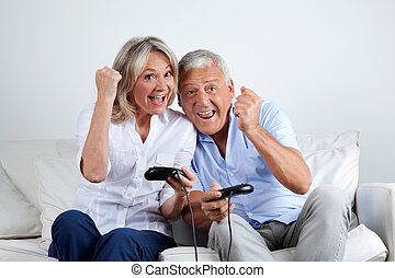 Couple Having Fun Playing Video Game - Senior couple having...