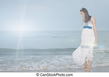 A girl stands on the beach and looks down on nature...