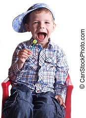 boy with an open mouth with a lollipop in his hand on a light background