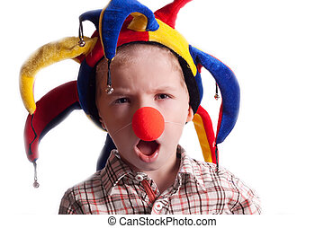 A little boy with a clown nose clown in a hat on a white...