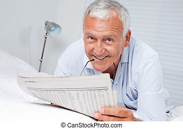 Man Reading Newspaper on Bed - Portrait of senior man...