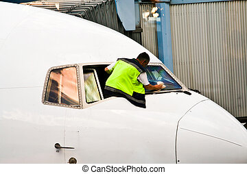worker is cleaning the cockpit window of an aircraft