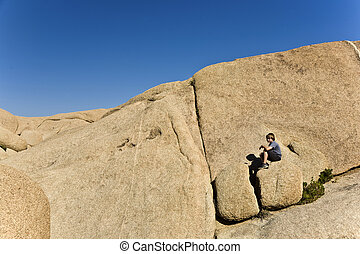 boy sitting on a rock - boy sitting on a big rock