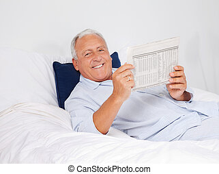 Relaxed Man Reading Newspaper - Portrait of relaxed senior...