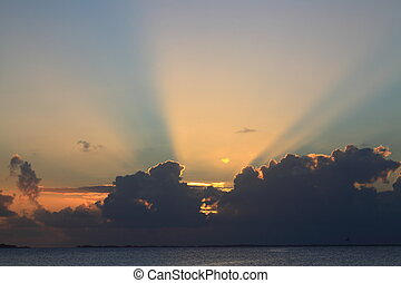 Sunset with Sunbeams at Manihi Atoll in the South Pacific with Coconut Trees