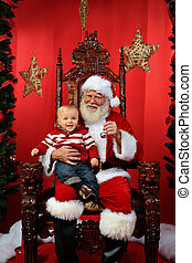 Baby Sitting on Santa's Lap - Baby boy sitting on Santa's...
