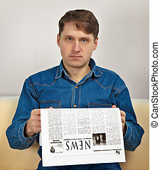 Man reads newspaper - A man reads evening newspaper at home...