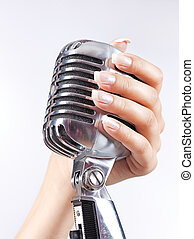 Big microphone in woman's hand - Big retro microphone in...