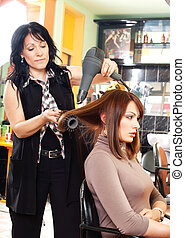 Hairdresser and the girl - Pretty lady sitting while...