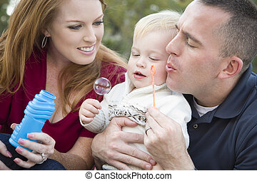 Young Parents Blowing Bubbles with their Child Boy in Park