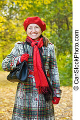 mature woman in autumn park - Portrait of mature woman with...