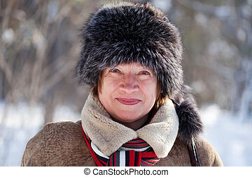 woman wearing fur cap - mature woman wearing winter coat and...
