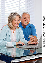Couple Shopping From Home - Senior couple making online...