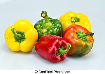 five capsicums on bluish surface - five different colors...