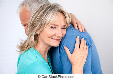 Couple Embracing - Woman embracing her husband with smile