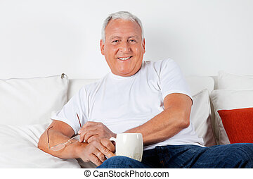 Relaxed Senior Man Having with Warm Drink
