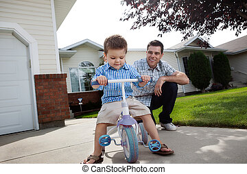 Father teaching Son To Ride a Tricycle - Happy father...