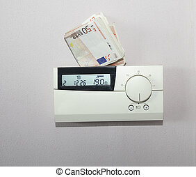Energy and power money - Euro bills behind the thermostat of...