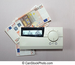Saving money for energy - Euro bills behind the thermostat...
