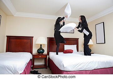 Female Executives Playing Pillow Fight - Two female...