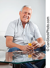 Senior Man Holding Glass of Orange Juice
