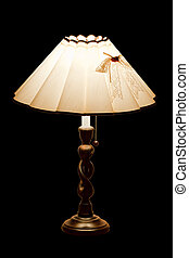classic table lamp with lights on, isolated on a black...
