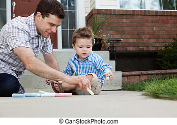 Father Drawing With Chalk on Ground - Young father drawing...