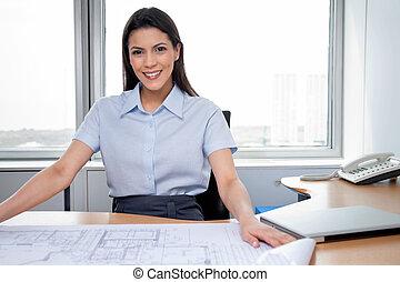 Female Architect Sitting With Blueprints On Desk