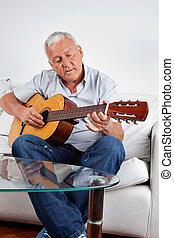 Man Playing Guitar - Senior man playing acoustic guitar at...