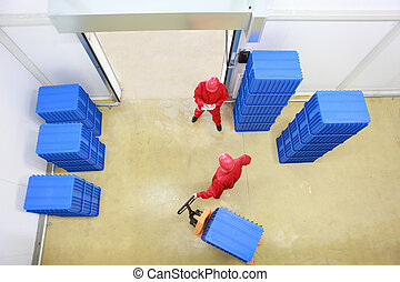 goods delivery in storehouse - overhead view of two workers...